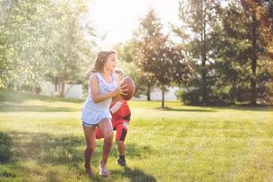 Girl and boy playing American footballの写真素材 [FYI03564597]