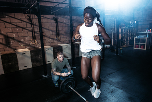 Trainer observing cross training athlete jumping over barbell in gymの写真素材 [FYI03564716]
