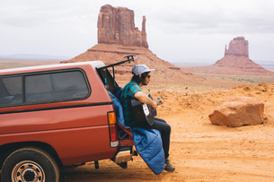 Young man sitting on four wheel drive boot playing acoustic guitar, Monument Valley, Arizona, USAの写真素材 [FYI03564801]