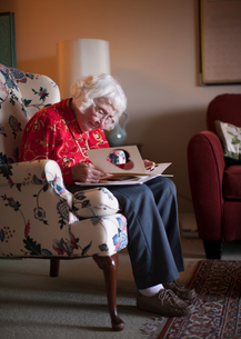Senior woman sitting in chair, looking at greeting cardの写真素材 [FYI03564833]