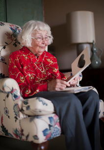Senior woman sitting in chair, looking at greeting cardの写真素材 [FYI03564837]