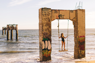 Woman standing on swing, Old Davenport Pier, Santa Cruz, California, USAの写真素材 [FYI03564866]