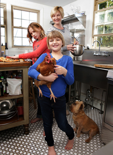 Mother and daughters in kitchen preparing folder, younger daughter holding pet chickenの写真素材 [FYI03564893]