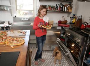 Young girl in kitchen, putting pizza in ovenの写真素材 [FYI03564894]