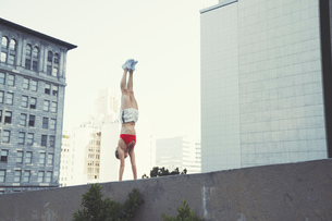 Young woman doing handstand on wall outdoorsの写真素材 [FYI03564990]