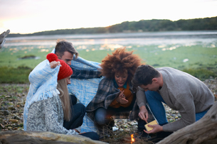 Four adult friends igniting campfire on beachの写真素材 [FYI03565116]