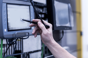 Engineer in engineering plant, using stylus on screen, close-upの写真素材 [FYI03565149]