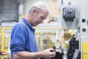 Engineer holding metal device in engineering plantの写真素材 [FYI03565160]