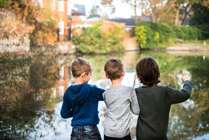 Three young boys, standing beside lake, rear viewの写真素材 [FYI03565188]