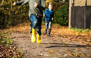Three boys, running along pathway in autumn, low sectionの写真素材 [FYI03565200]