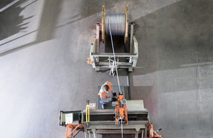 Worker winding electrical cables at cable storage facility, overhead viewの写真素材 [FYI03565328]