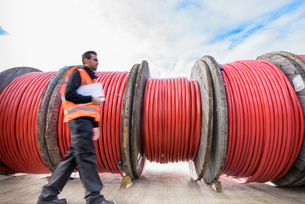 Worker walking past reels of electrical cable at cable storage facilityの写真素材 [FYI03565333]