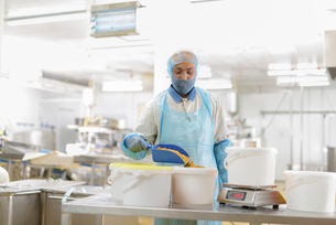 Male worker weighing curry powder in Asian food factoryの写真素材 [FYI03565359]