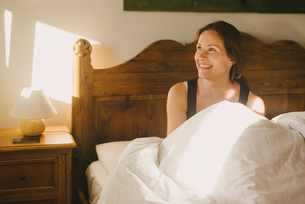 Woman smiling in bedの写真素材 [FYI03565368]
