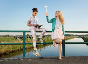 Children using miniature wind turbine to power digital tablet, Breda, Netherlandsの写真素材 [FYI03565522]