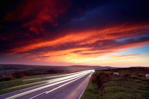 Headlight trails on moorland road at sunset, Reynoldston, Gower, Walesの写真素材 [FYI03565544]