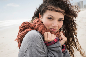 Portrait of young woman wrapped in scarf on windy beach, Western Cape, South Africaの写真素材 [FYI03565579]