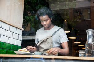 Waiter preparing order at cafe windowの写真素材 [FYI03565617]