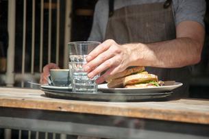 Cropped shot of waiter preparing order at cafe windowの写真素材 [FYI03565618]