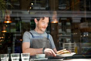 Waiter preparing order at cafe windowの写真素材 [FYI03565620]