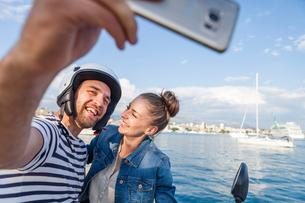 Young moped couple taking selfie on harbour, Split, Dalmatia, Croatiaの写真素材 [FYI03565709]