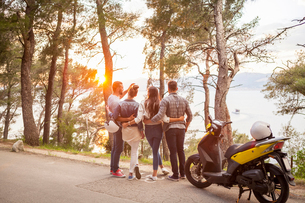 Two couples with moped looking out at sunset from coastal road, Split, Dalmatia, Croatiaの写真素材 [FYI03565722]
