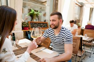 Young couple raising a wine toast at sidewalk restaurant, Split, Dalmatia, Croatiaの写真素材 [FYI03565723]