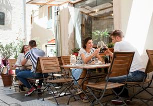 Young couples raising a wine toast at sidewalk restaurant, Split, Dalmatia, Croatiaの写真素材 [FYI03565727]