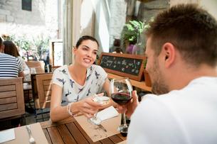 Young couple raising a wine toast at sidewalk restaurant, Split, Dalmatia, Croatiaの写真素材 [FYI03565728]