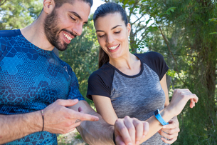 Male and female runners checking smartwatches in park, Split, Dalmatia, Croatiaの写真素材 [FYI03565745]