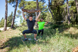 Two young men doing weightlifting training with logs in forest, Split, Dalmatia, Croatiaの写真素材 [FYI03565763]
