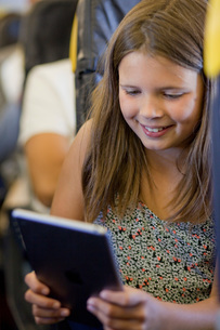 Young girl using digital tablet in airplaneの写真素材 [FYI03565806]