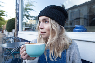 Young woman sitting outside cafe, drinking cup of teaの写真素材 [FYI03565926]