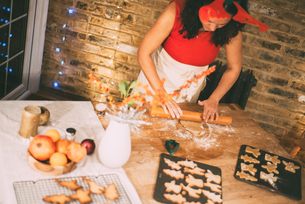 Mature woman rolling Christmas cookie pastry at kitchen counterの写真素材 [FYI03565977]