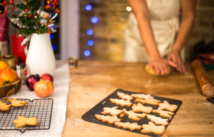 Mid section of woman flattening Christmas cookie pastry at kitchen counterの写真素材 [FYI03565978]