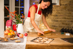Mature woman rolling Christmas cookie pastry at kitchen counterの写真素材 [FYI03565979]