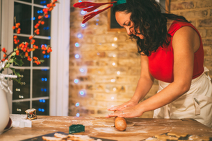 Mature woman rolling Christmas cookie pastry at kitchen counterの写真素材 [FYI03565980]