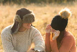 Young couple sitting in rural setting, wearing warm hatsの写真素材 [FYI03566127]