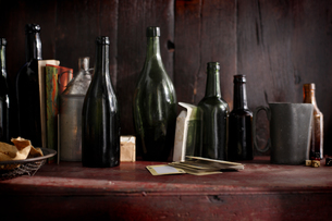 Empty vintage beer bottles and playing cards on pub shelfの写真素材 [FYI03566208]