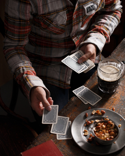 Cropped shot of man playing cards at pub tableの写真素材 [FYI03566214]