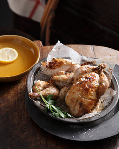 Bistro meal of roast chicken in a basket with parsley on tableの写真素材 [FYI03566215]