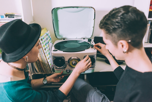 Over shoulder view of two young women playing vinyl on vintage turntableの写真素材 [FYI03566312]