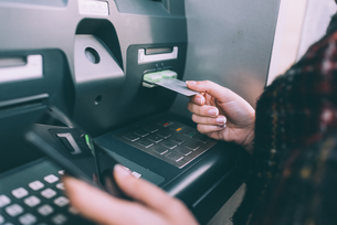 Hand of young woman inserting credit card into cash machineの写真素材 [FYI03566336]