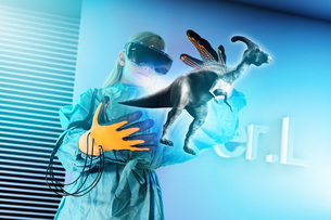 Girl in virtual reality headset interacting with digital floating dinosaurの写真素材 [FYI03566342]
