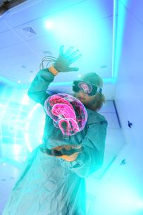 Boy in virtual reality headset interacting with digital floating human brainの写真素材 [FYI03566347]