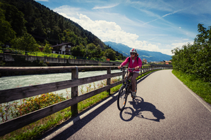 Female cyclist cycling along path by river in Vinschgau Valley, South Tyrol, Italyの写真素材 [FYI03566365]