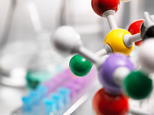 A molecular model of a chemical formula with laboratory equipment in the backgroundの写真素材 [FYI03566613]