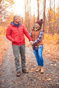 Mature couple walking along rural pathway, in autumnの写真素材 [FYI03566729]