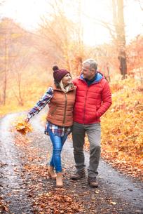 Mature couple walking along rural pathway, in autumnの写真素材 [FYI03566731]