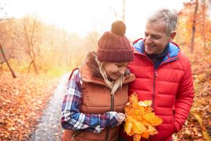 Mature couple walking along rural pathway, in autumnの写真素材 [FYI03566735]